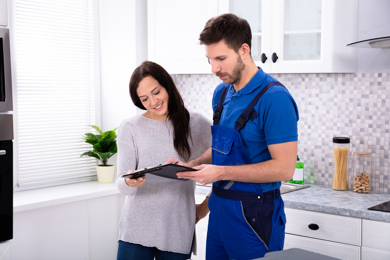Male Plumber Showing Invoice To Woman